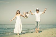 Familia feliz que camina en la playa en el tiempo del día Fotografía de archivo libre de regalías