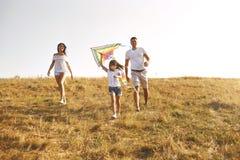 Familia feliz que camina en naturaleza en la puesta del sol en verano imagenes de archivo