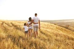 Familia feliz que camina en naturaleza en la puesta del sol en verano imagen de archivo