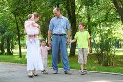 Familia feliz que camina en parque de la ciudad, el grupo de cinco personas, la estación de verano, el niño y el padre Imágenes de archivo libres de regalías