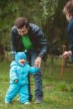 Familia feliz que camina en parque del otoño: madre, padre y su pequeño hijo - aprenda dar un paseo independientemente fotografía de archivo