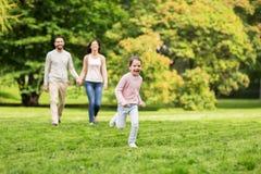 Familia feliz que camina en parque del verano y que se divierte Fotos de archivo