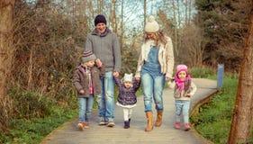 Familia feliz que camina juntas llevando a cabo las manos en Fotografía de archivo libre de regalías