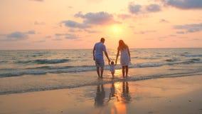 Familia feliz que camina a lo largo de la costa de mar en la puesta del sol almacen de metraje de vídeo