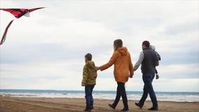 Familia feliz que camina a lo largo de la orilla El jugar del hombre, de la mujer, del niño pequeño y de la muchacha metrajes
