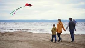 Familia feliz que camina a lo largo de la orilla El jugar del hombre, de la mujer, del niño pequeño y de la muchacha almacen de metraje de vídeo