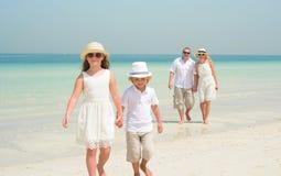 Familia feliz que camina a lo largo de una playa Fotografía de archivo libre de regalías