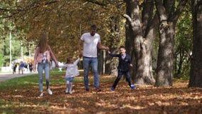 Familia feliz que camina a lo largo del carril del parque en un día del otoño cámara lenta 4k metrajes