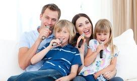 Familia feliz que canta un Karaoke junto Imagen de archivo libre de regalías