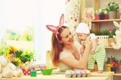 Familia feliz que celebra la madre y al bebé de pascua con los oídos del conejito Imagenes de archivo