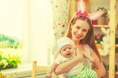 Familia feliz que celebra la madre y al bebé de pascua con los oídos del conejito Fotos de archivo