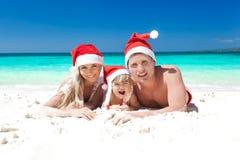 Familia feliz que celebra la Navidad en la playa Imágenes de archivo libres de regalías