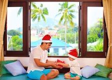 Familia feliz que celebra Navidad en las zonas tropicales Foto de archivo libre de regalías