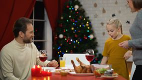 Familia feliz que cena sano Navidad, decoraciones que chispean en el árbol, día de fiesta almacen de video