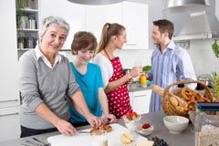 Familia feliz que cocina así como la abuela Foto de archivo libre de regalías