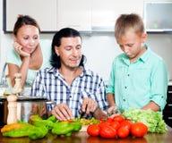 Familia feliz que cocina el almuerzo veggy Fotografía de archivo libre de regalías