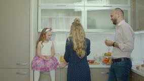 Familia feliz que cocina junto en la cocina almacen de metraje de vídeo