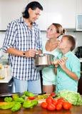 Familia feliz que cocina la comida junta Foto de archivo