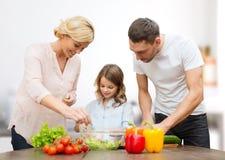 Familia feliz que cocina la ensalada vegetal para la cena Foto de archivo libre de regalías