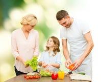 Familia feliz que cocina la ensalada vegetal para la cena Imagen de archivo libre de regalías