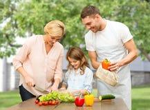 Familia feliz que cocina la ensalada vegetal para la cena Fotos de archivo libres de regalías