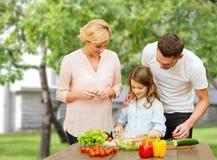 Familia feliz que cocina la ensalada vegetal para la cena Imagenes de archivo