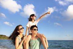 Familia feliz que coloca en el reloj de la playa la puesta del sol fotografía de archivo libre de regalías