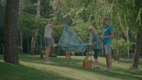 Familia feliz que coloca la manta de la comida campestre en el parque almacen de video