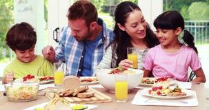 Familia feliz que come el almuerzo junto metrajes