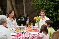 Familia feliz que come en el jardín Foto de archivo