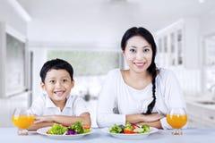 Familia feliz que come ensalada en la cocina imagenes de archivo