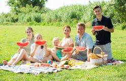 Familia feliz que come la sandía al aire libre Imágenes de archivo libres de regalías