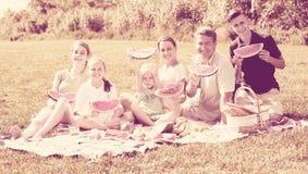 Familia feliz que come la sandía al aire libre Fotos de archivo libres de regalías
