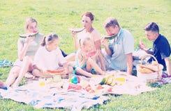 Familia feliz que come la sandía al aire libre Imagen de archivo