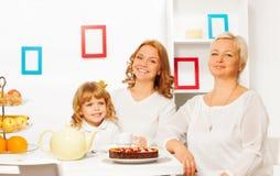 Familia feliz que come la torta y que bebe té Imágenes de archivo libres de regalías