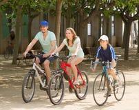 Familia feliz que completa un ciclo en unidad del parque Imágenes de archivo libres de regalías