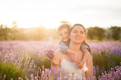 Familia feliz que consiste en la madre bonita y el niño alegre que sueñan sentarse junto entre el campo del verano de la lavanda  Fotografía de archivo