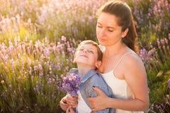 Familia feliz que consiste en la madre hermosa y el niño alegre que sueñan sentarse junto entre el campo del verano de flores Foto de archivo