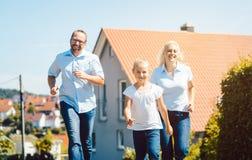 Familia feliz que corre delante de su nuevo hogar imagen de archivo