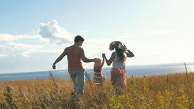 Familia feliz que corre en el campo