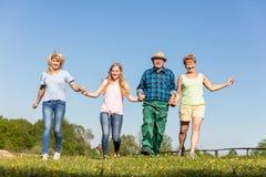 Familia feliz que corre en el campo generaciones Imagen de archivo libre de regalías