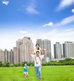Familia feliz que corre en el parque de la ciudad Foto de archivo