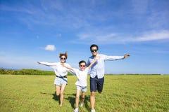 Familia feliz que corre junto en la hierba Foto de archivo libre de regalías
