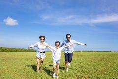 Familia feliz que corre junto en la hierba Fotografía de archivo