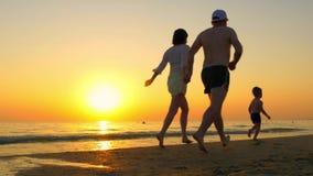 Familia feliz que corre a lo largo de la playa del mar en la puesta del sol almacen de metraje de vídeo