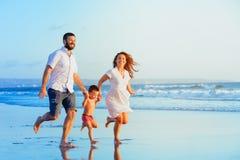 Familia feliz que corre por la playa de la puesta del sol fotos de archivo