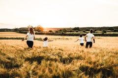 Familia feliz que corre a través del campo Familia que tiene campo de la diversión foto de archivo