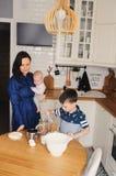 Familia feliz que cuece junto en cocina blanca moderna Hija de la madre, del hijo y del bebé que cocina por mañana acogedora del  Foto de archivo