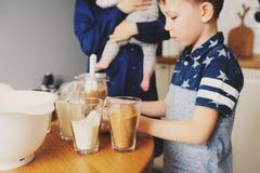 Familia feliz que cuece junto en cocina blanca moderna Hija de la madre, del hijo y del bebé que cocina por mañana acogedora del  Fotos de archivo