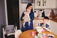 Familia feliz que cuece junto en cocina blanca moderna Hija de la madre, del hijo y del bebé que cocina por mañana acogedora del  Imagenes de archivo